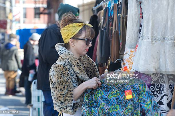 Woman with leopard print coat, sunglasses and yellow scarf goes through clothing at the Hells Kitchen Flea Market in Hells Kitchen, New York City