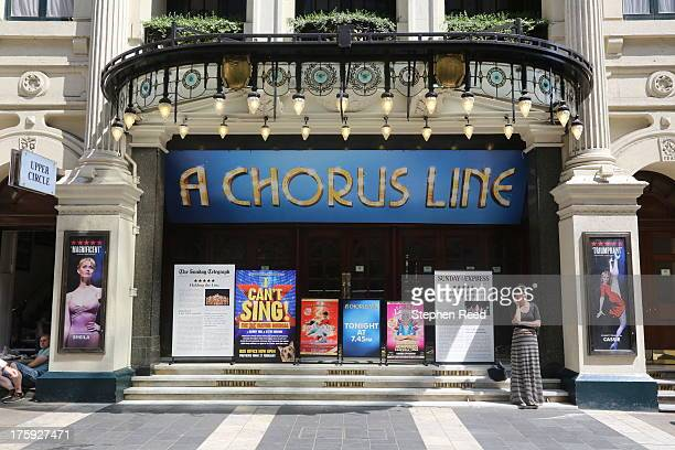Woman with lines in her skirt waits outside the theater where the musical A Chorus Line is showing in the West End, London, England.