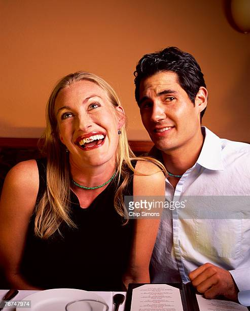 Woman with lipstick stain on teeth with man