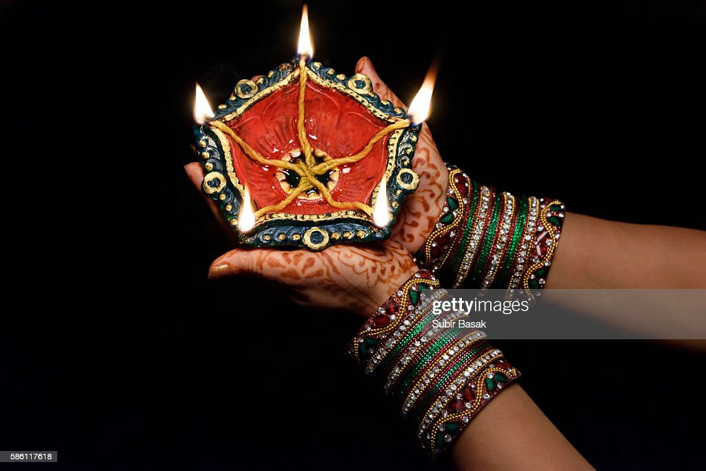 Woman with lit earthen lamp at Diwali festival,India. : Stock Photo