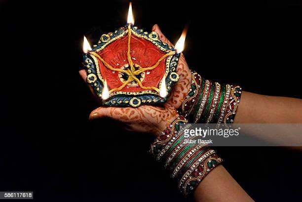 woman with lit earthen lamp at diwali festival,india. - diwali celebration stock photos and pictures