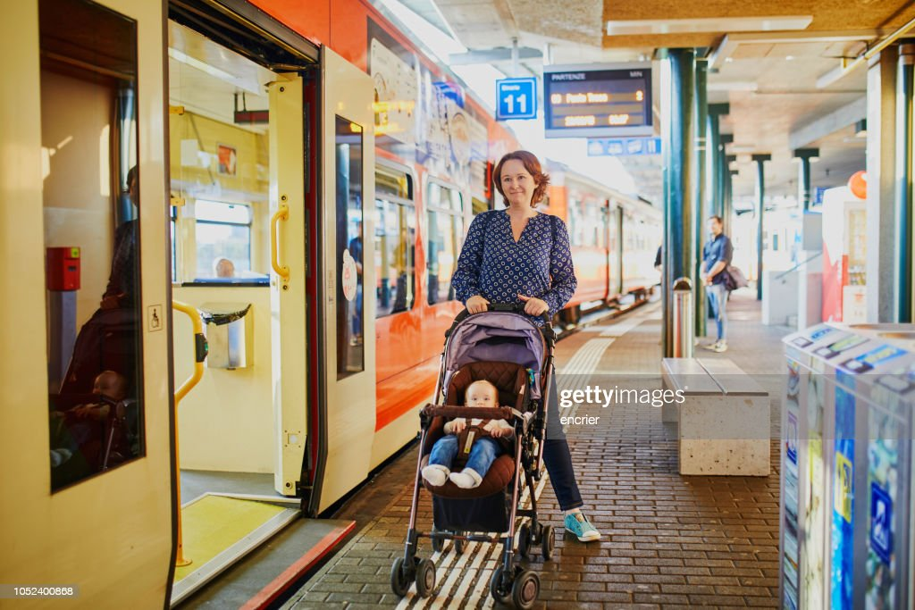 Woman with little girl at railway station : Stock Photo