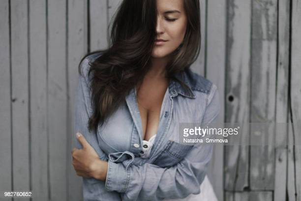 woman with long black hair obscuring face in denim shirt - 胸の谷間 ストックフォトと画像
