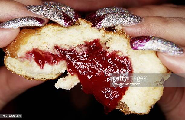 Woman with long glittery nails eating jam doughnut, close-up