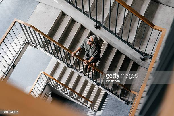 Woman with long grey hair in staircase