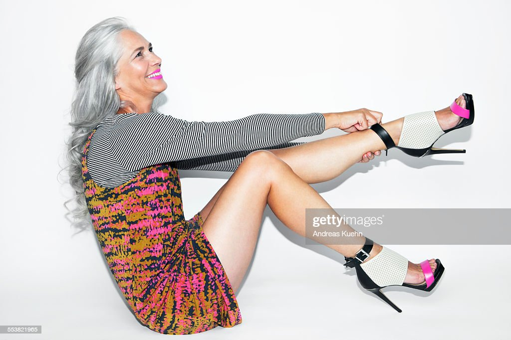 Woman with long, grey hair sitting and laughing. : Stock Photo
