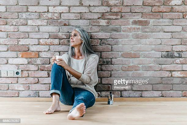 Woman with long grey hair sitting on the floor at brick wall