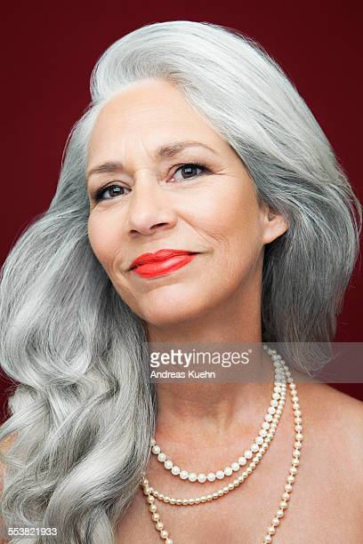 Woman with long, grey hair wearing pearls.