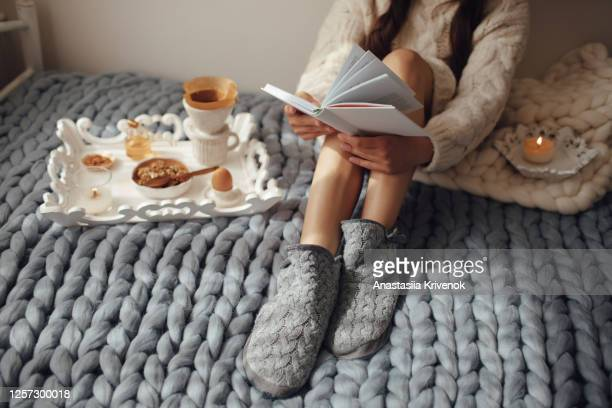 woman with long hair drinking hot coffee and reading book in bed. woman in woolen socks and sweater sitting on wool chunky merino plaid. cozy winter morning concept. - blanket stock pictures, royalty-free photos & images