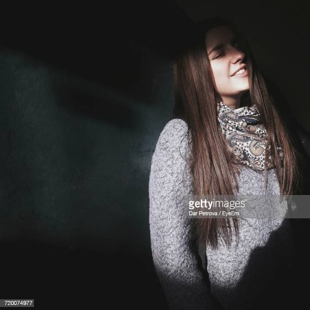 Woman With Long Hair Standing By Wall