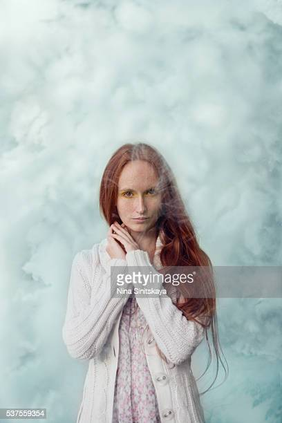 woman with long red hair, freckles and in white clothes standing in a blue smoke - thick white women stock photos and pictures