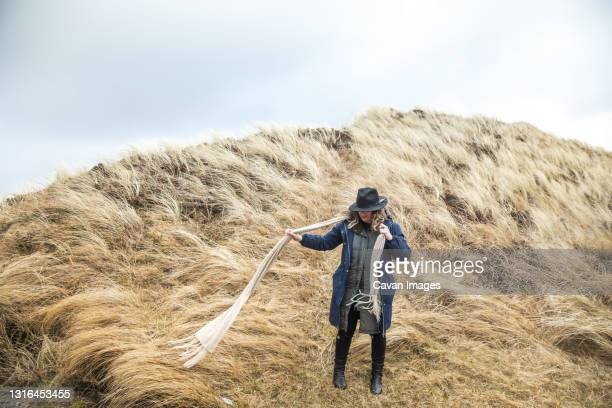 woman with long scarf in sea grass on a windy day in denmark - denmark stock pictures, royalty-free photos & images