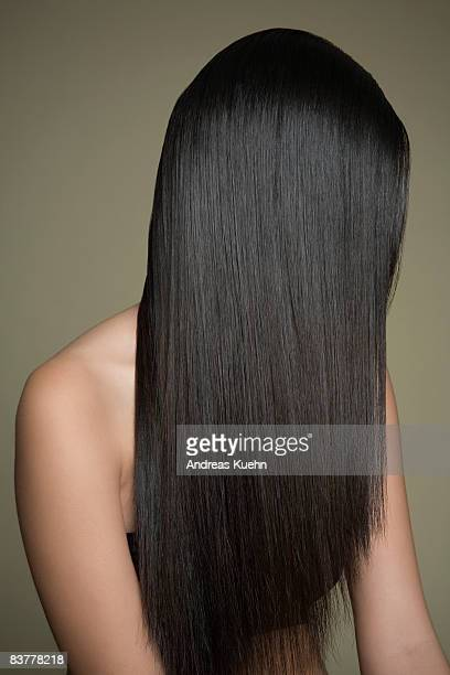 woman with long, shiny hair covering face. - straight hair stock pictures, royalty-free photos & images