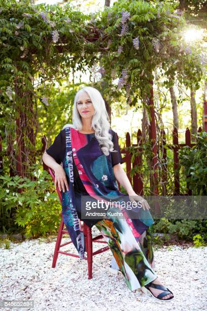 Woman with long, silvery, grey hair wearing a fashionable outfit sitting on a red wooden chair in front of here flower garden on a sunny summer day.