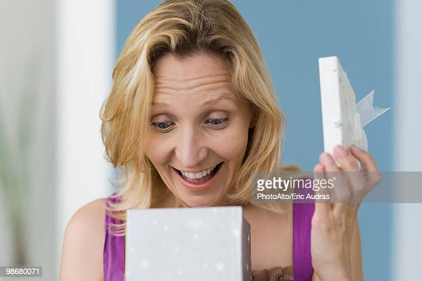 Woman with look of surprise opening gift