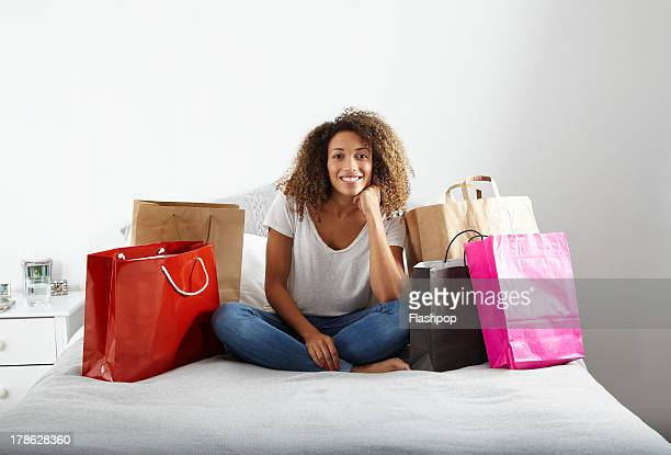 Woman with lots of shopping bags sitting on bed