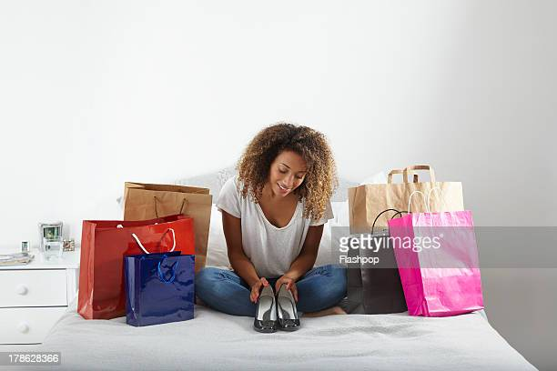 woman with lots of shopping bags sitting on bed - high heels stock pictures, royalty-free photos & images