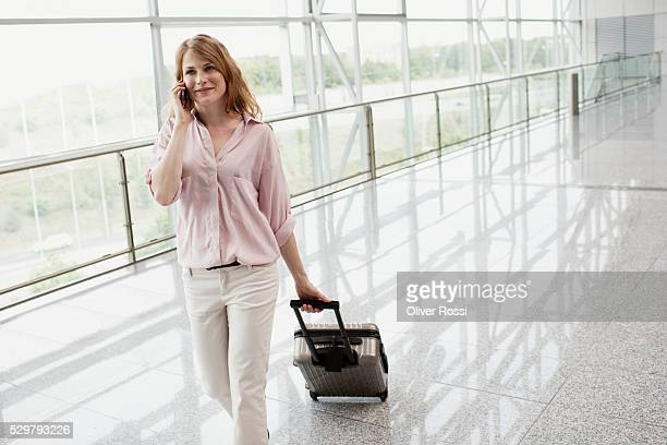 Woman with luggage in airport lobby
