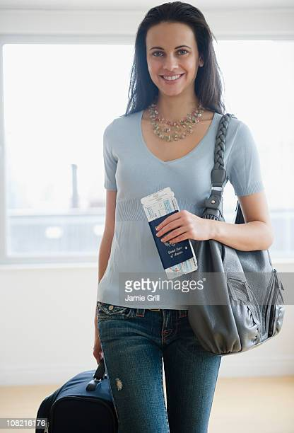 Woman with luggage, passport and airline tickets