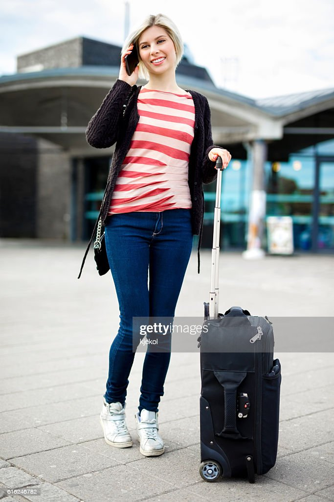 Woman With Luggage Talking On Mobile Phone Outside Railroad Stat : Stock Photo