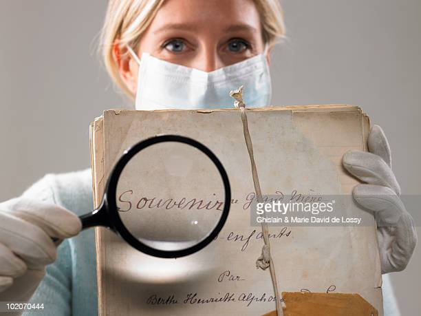 woman with magnifying glass showing file - museum curator stock pictures, royalty-free photos & images