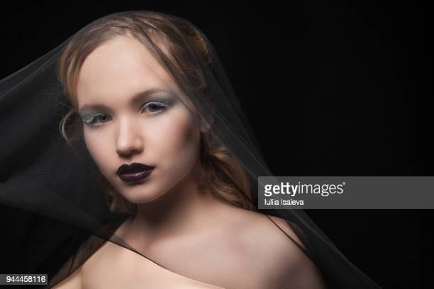 Woman with makeup under black veil