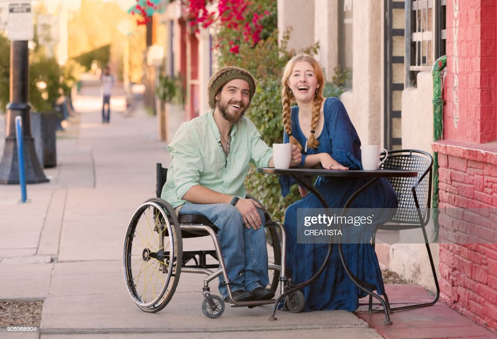 Woman with Man in Wheelchair at Cafe Table : Foto de stock
