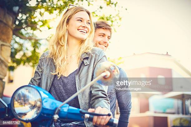 Woman with man riding scooter in city