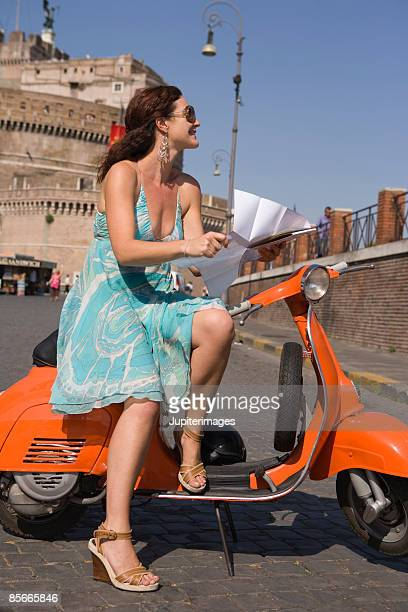 Woman with map on motor scooter , Saint Angel Castle , Rome , Italy