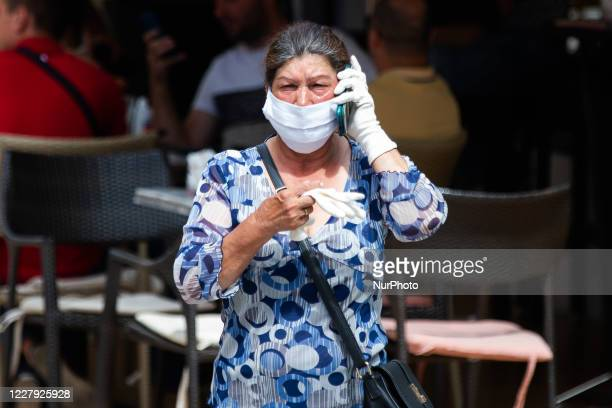 Woman with mask and gloves walks through the city during the new Coronavirus disease after the decrease of coronavirus infected in Belgrade, Serbia...