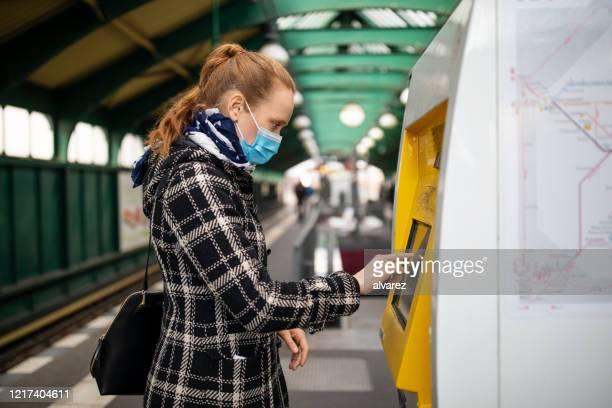 frau mit maske kauft ein zugticket am automaten - abstand halten infektionsvermeidung stock-fotos und bilder