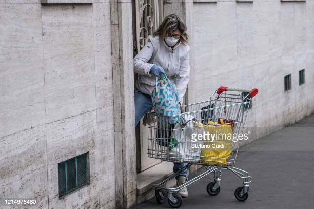 Woman with mask comes home after shopping on March 26 2020 in Turin Italy The Italian government continues to enforce the nationwide lockdown...