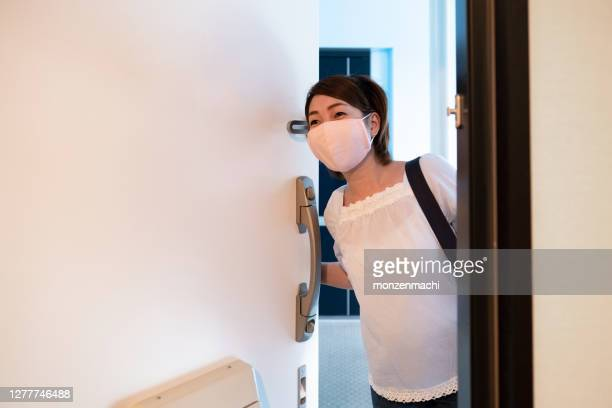 マスクを持った女性が家に帰ってくる - 建物入口 ストックフォトと画像