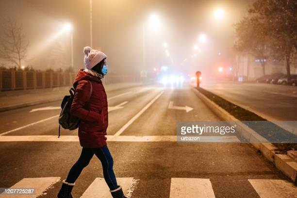 woman with mask crossing street - pedestrian stock pictures, royalty-free photos & images