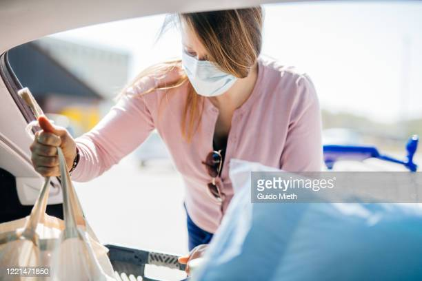 woman with mask doing shopping while covid-19. - guido mieth stock pictures, royalty-free photos & images
