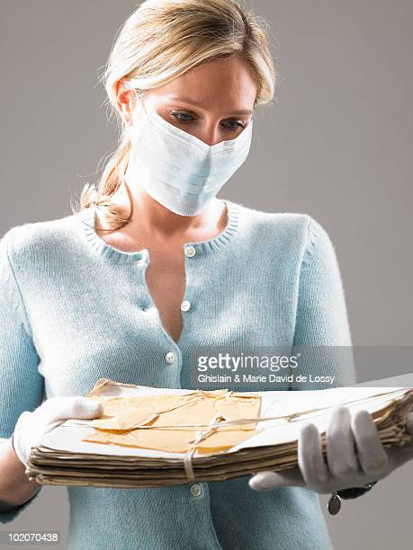 Woman with mask, holding precious files