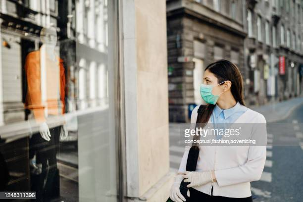 woman with mask looking at a closed fashion clothes storefront.clothing shopping during coronavirus outbreak shutdown.covid-19 quarantine apparel retail store closures.small business loss concept. - economic stimulus stock pictures, royalty-free photos & images