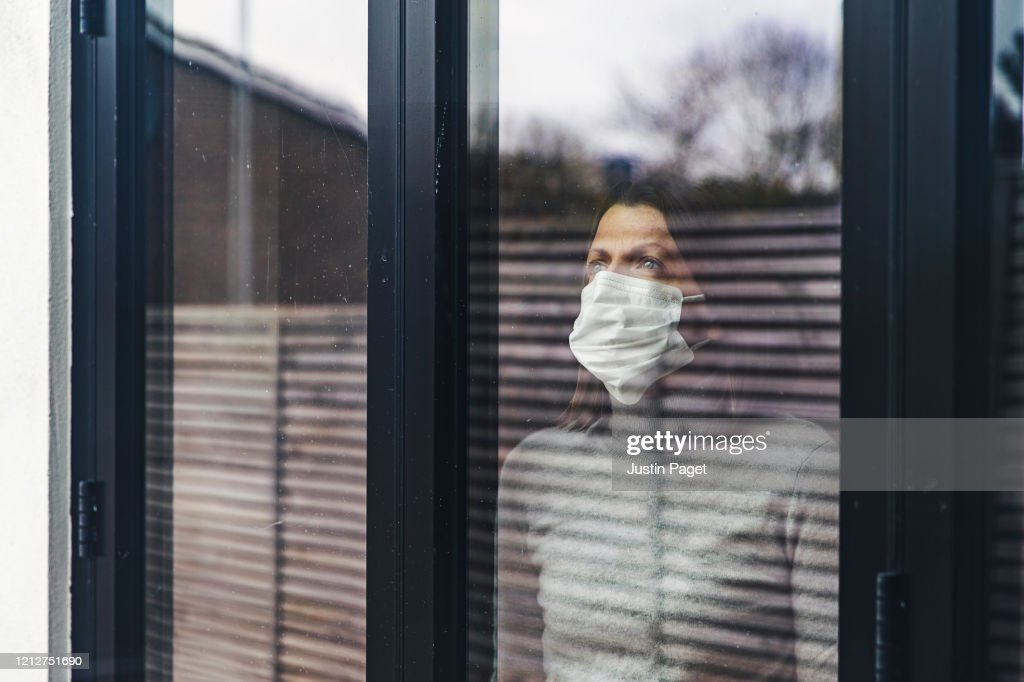 Woman with mask looking out of window : Stock Photo