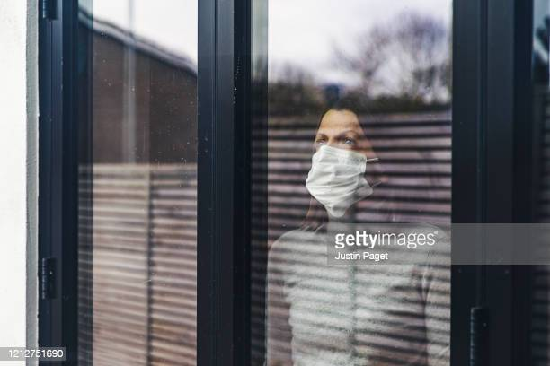 woman with mask looking out of window - trapped stock pictures, royalty-free photos & images