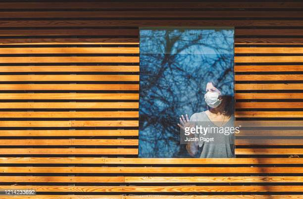 woman with mask looking through window - cold and flu stock pictures, royalty-free photos & images