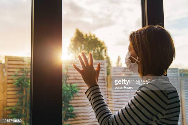 woman with mask looking through window - loneliness stock pictures, royalty-free photos & images