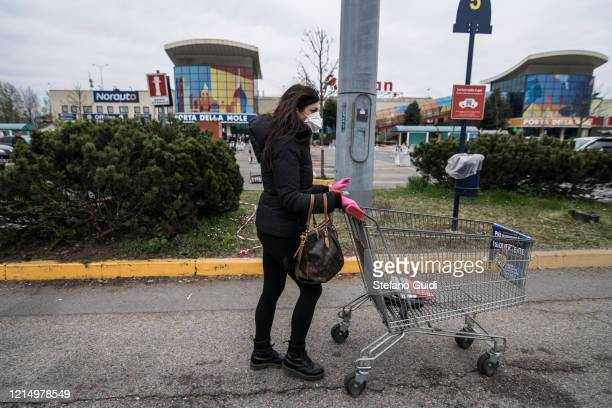 Woman with mask outside a supermarket for grocery shopping on March 26 2020 in Turin Italy The Italian government continues to enforce the nationwide...