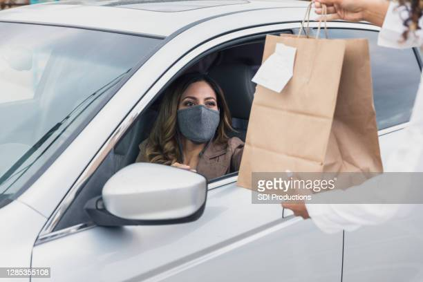 woman with mask receives curbside delivery during covid-19 - curbside pickup stock pictures, royalty-free photos & images