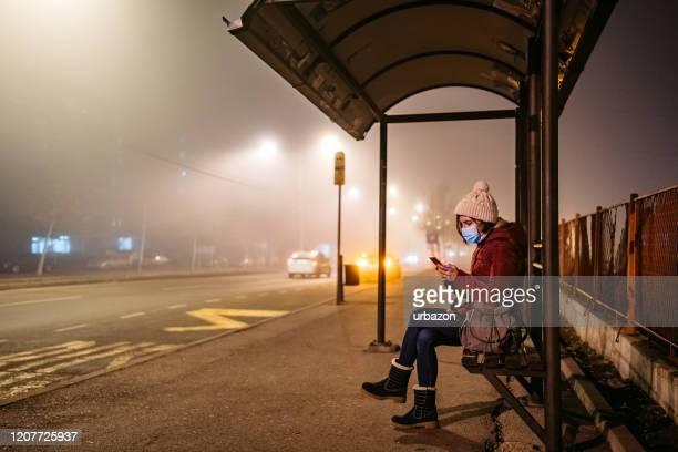 vrouw met masker dat telefoon op bushalte gebruikt - luchtvervuiling stockfoto's en -beelden