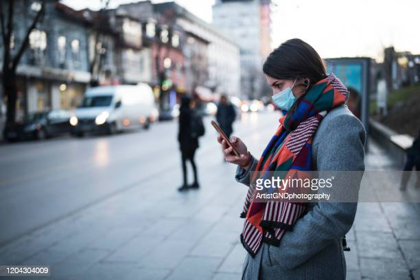 woman with mask using phone on the street. - coronavirus stock pictures, royalty-free photos & images