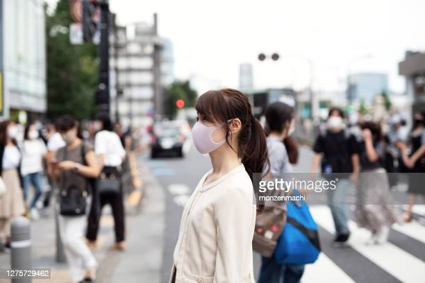 混雑した通りを歩くマスクを持つ女性 - コンセプト ニューノーマル ストックフォトと画像