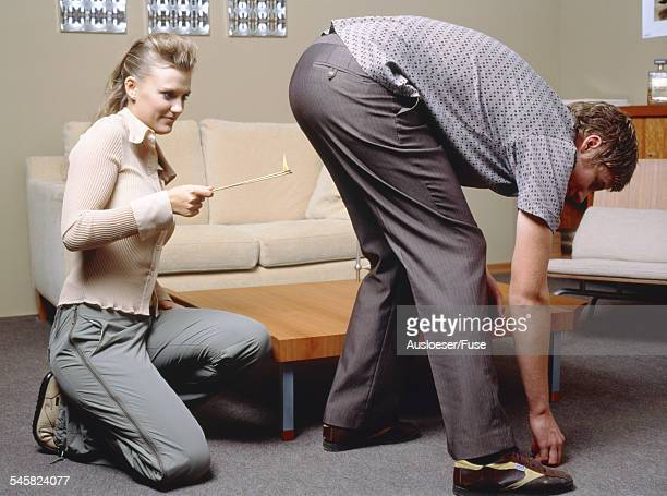 Woman with match, man bending over