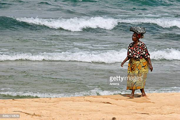 Woman with merchandise on her head walking on the beach of Lake Malawi Malawi Africa