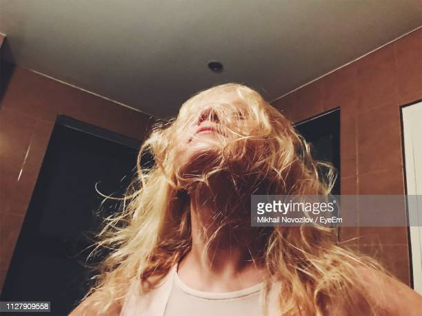 woman with messy blond hair at home - crazy hair stock pictures, royalty-free photos & images