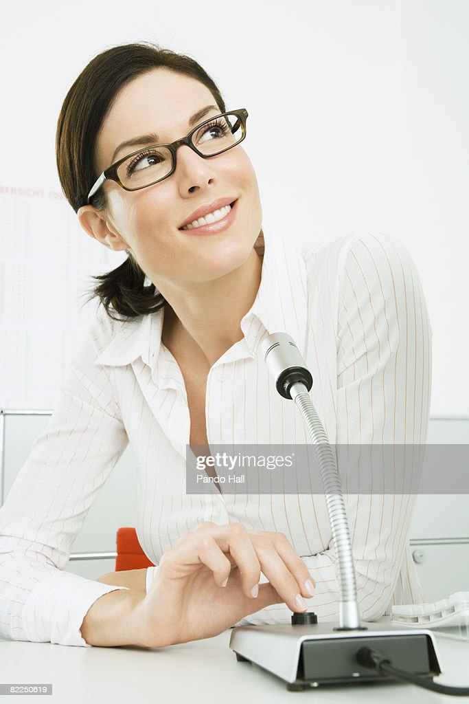 Woman with microphone on desk : Stock Photo